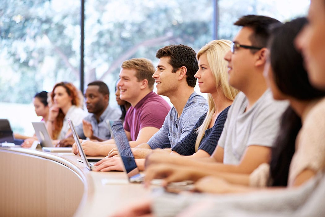 Group of multi-racial students smiling in class